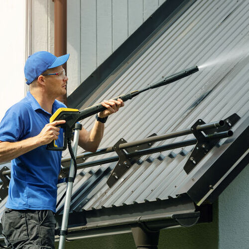 A Roofer Cleans a Roof as Part of Roof Maintenance.