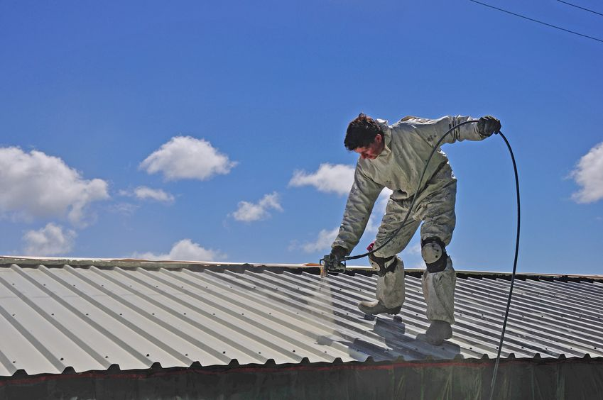 A Picture of a Man Spraying a Roof.