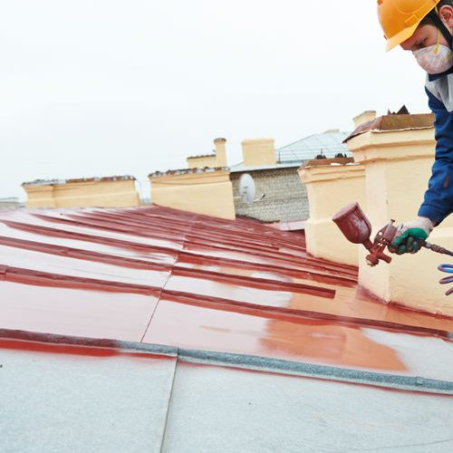 A Picture of a Roofer Spraying a Red Metal Roof.